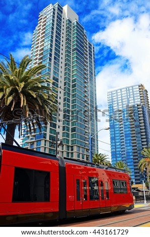 scenic cityscape of modern city with residential apartment towers palm trees and public city trolley on foreground against attractive light blue sky detail vertical view - stock photo