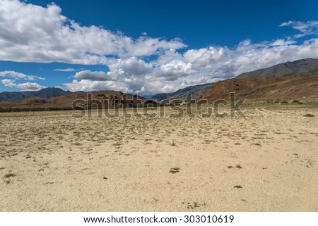 Scenic desert steppe landscape with mountains. Dry land with rare plants as the foreground and mountains, sky and clouds in the background.