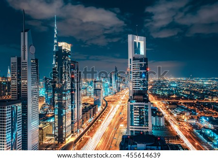 Scenic Dubai downtown architecture. Nighttime skyline with illuminated skyscrapers and highway. Fantastic travel background.