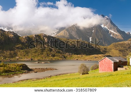 Scenic fjord on Lofoten islands with typical fishing hut and towering mountain peaks - stock photo