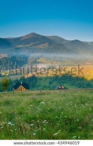 Scenic foggy sunrise in the mountain village. Beautiful Sunny summer landscape.