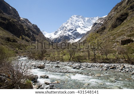 Scenic French Alps view in the springtime of a river and a snow covered mountain peak - stock photo