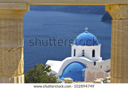 Scenic Greek church in front of an ancient classical temple on an island  at the mediterranean aegean sea.