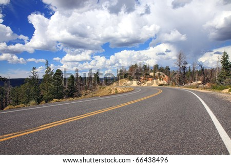 Scenic highway through Bryce National Park with dramatic cumulus cloud cloudscape against blue sky overhead - stock photo