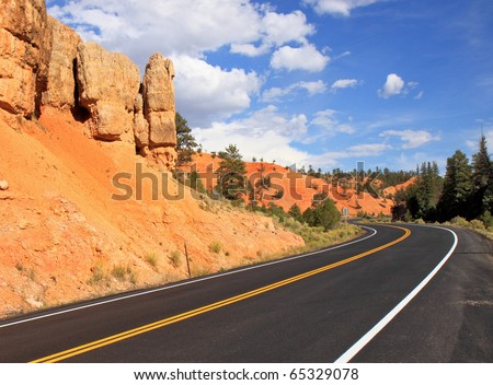 Scenic highway winds through red sandstone spires in Red Canyon, near Bryce National Park - stock photo