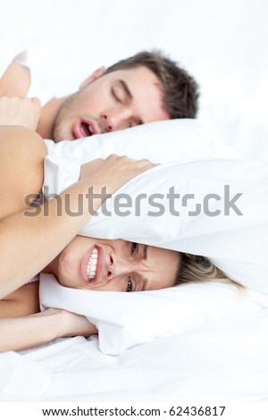 Scenic in bedroom of loving young couple lying in bed and holding pillow on the ears because of snoring boyfriend. - stock photo