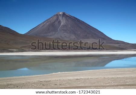 "Scenic lagoon in Bolivia Laguna Verde (Spanish ""green lake"") is a salt lake located on the Chilean border at the foot of the volcano Licancabur in Eduardo Avaroa Andean Fauna National Reserve. - stock photo"