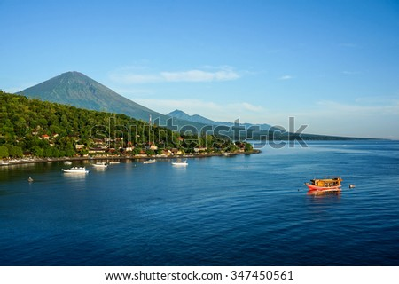 Scenic lagoon with boats in small village Amed on the east of Bali, Indonesia. Volcano Gunung Agung on background. - stock photo