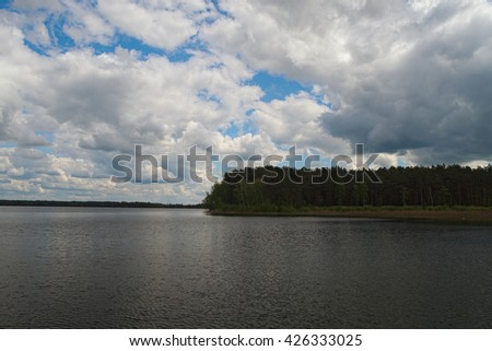 Scenic lake and forest.White clouds of different shapes are closing blue sky and sun (Pisochne ozero, Ukraine). - stock photo