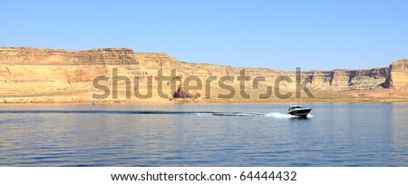 Scenic Lake Powell in Glen Canyon has an abundance of water sport opportunities. The blue lake is populated with house boats, jet skis, and fishermen. It's dotted with red sandstone cliff formations. - stock photo