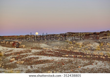 Scenic landscape in Painted desert and Petrified forest national park with full moon, Arizona, USA - stock photo