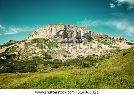 Scenic Landscape View of Natural Rock Formation in Mountainous Alpine Region with Lush Green Valley and Blue Sky - stock photo