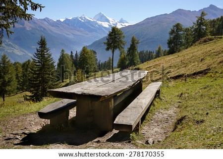 Scenic landscape with empty rustic picnic table and benches made of lumber on a grassy slope with coniferous trees and snow-capped Matterhorn mountain at the horizon, in Valais, Alps, Switzerland. - stock photo