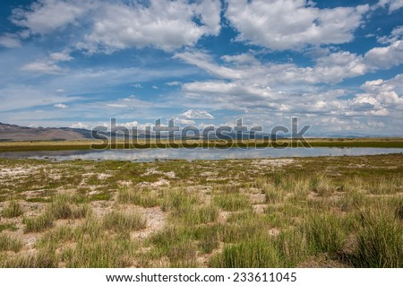 Scenic landscape with lake in steppe on a background of mountains, blue sky and clouds - stock photo