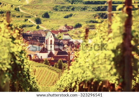 Scenic mountain landscape with vineyards growing on hills and old church in Germany, Black forest, Kaiserstuhl. Toned, vintage effect.  - stock photo