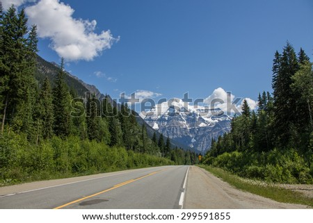 Scenic mountain road with blue sky - stock photo