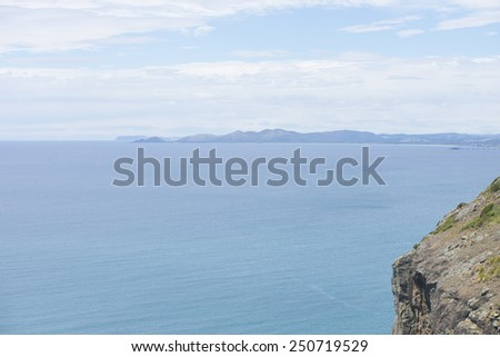 Scenic ocean panorama view from cliff lookout on north coast of Tasmania Australia at Bass Strait, with mountains as blurred background at horizon and copy space. - stock photo