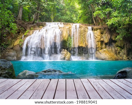 Scenic of waterfall and wood bridge surrounded by lush plant. - stock photo