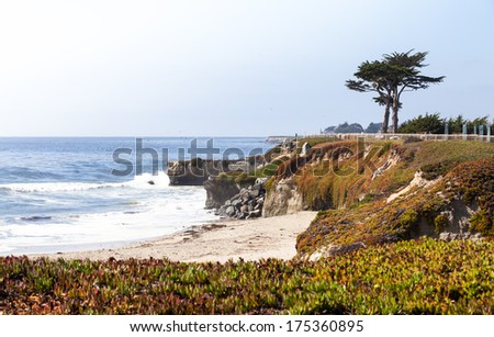 Scenic Pacific ocean coastline with rocky hills and small beach - stock photo