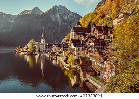 Scenic picture-postcard view of famous Hallstatt mountain village with Hallstatter See in the Alps in beautiful golden morning light in fall with retro vintage filter, region of Salzkammergut, Austria - stock photo