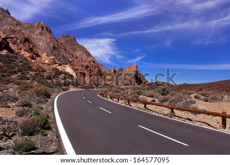 Scenic, picturesque curved mountain road with blue sky and white clouds on sunny day. (Tenerife, Canary islands, Spain). Travel (vacation) concept. Outdoor. Copy space.