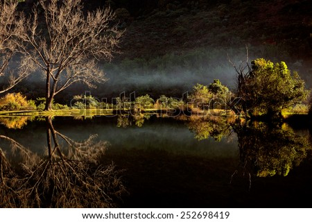 Scenic pond with  mist and reflection in water, Royal Natal National Park, South Africa - stock photo