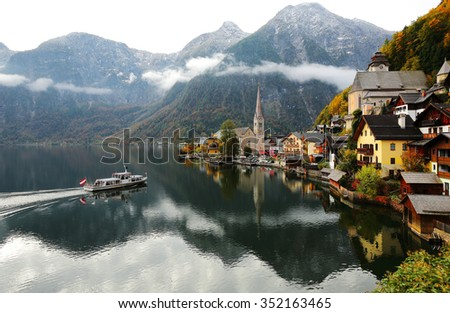 Scenic postcard view of famous Hallstatt village by Hallstattersee Lake in the Austrian Alps ~ Morning scenery of a sightseeing boat on the lake with beautiful reflections of mountains and village - stock photo