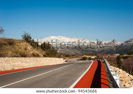 Scenic road bending across a sunny winter landscape - stock photo