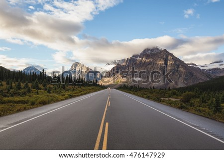 Scenic road through the Canadian Rockies, surrounded with rocky mountains. Taken in Banff National Park, Alberta, Canada, during a cloudy sunrise.