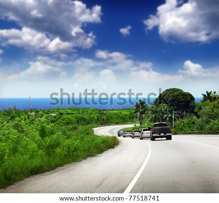 Scenic road with cars along a beautiful coast with bright blue sky - stock photo