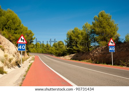 Scenic road with red bicycle lanes running across Mediterranean pine forest - stock photo