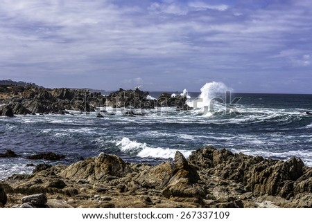 Scenic rocky coastline along the historic 17 Mile Drive in Pebble Beach California. Large waves crashing in the rocks. - stock photo