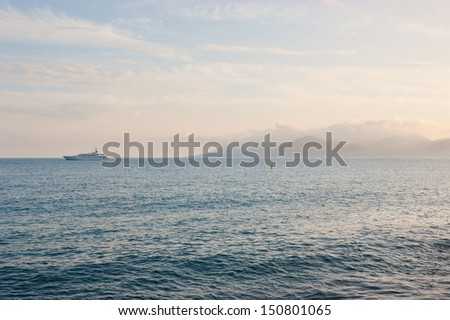 Scenic seascape with foggy mountains and yacht, Cannes, France. - stock photo