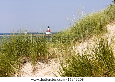 Scenic shot of dune and grass in St. Joseph, Michigan, with lighthouse in the distance. - stock photo