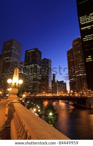 Scenic skyline view of the Chicago River after sunset.  Riverwalk area surrounded by historical skyscrapers with a deep blue sky in downtown Chicago. - stock photo