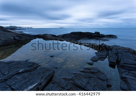 Scenic stone beach in A, Lofoten Islands, Arctic, Norway, Scandinavia, Europe on a cloudy, summer evening. - stock photo