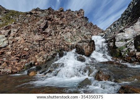 Scenic summer mountain landscape: beauty view of mountain river into steep cliffs on a background of blue sky with clouds on sunny day. Eurasia, Russian Federation, Far East, Kamchatka Peninsula. - stock photo