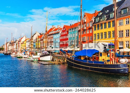 Scenic summer view of Nyhavn pier with color buildings, ships, yachts and other boats in the Old Town of Copenhagen, Denmark - stock photo