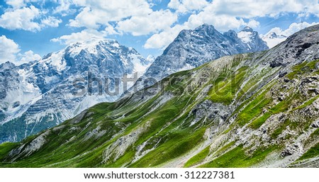 Scenic summer view of the snow covered mountaintops and grass covered hills at the Stelvio pass, Italy. - stock photo