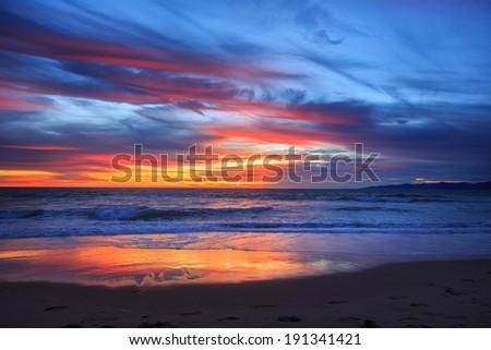 Scenic sunset over ocean beach - stock photo