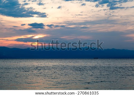 Scenic sunset over ocean beach - stock photo
