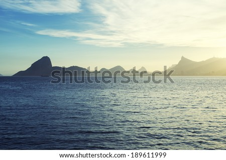 Scenic sunset view of Sugarloaf Pao de Acucar Mountain and mountain geography from across Guanabara Bay in Niteroi Rio de Janeiro Brazil