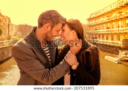 scenic tourists embracing eachother on a bridge - stock photo