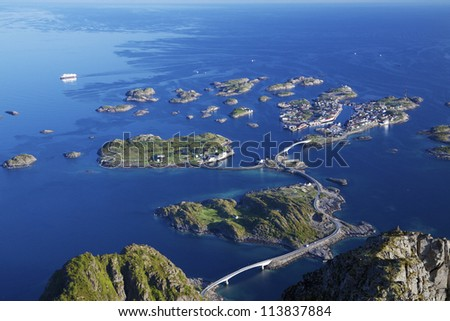 Scenic town of Henningsvaer on Lofoten islands in Norway with large fishing harbor and bridges connecting rocky islands