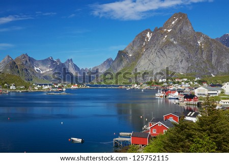 Scenic town of Reine, Norway on sunny summer day with picturesque fjord and surrounding mountain peaks