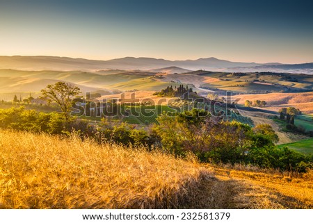 Scenic Tuscany landscape with rolling hills and harvest fields in golden morning light, Val d'Orcia, Italy - stock photo