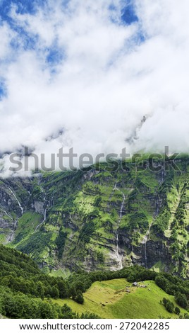 Scenic view af small alpine house among great mountain walls - stock photo