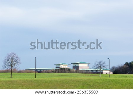 Scenic view at farm buildings under cloudy sky - stock photo
