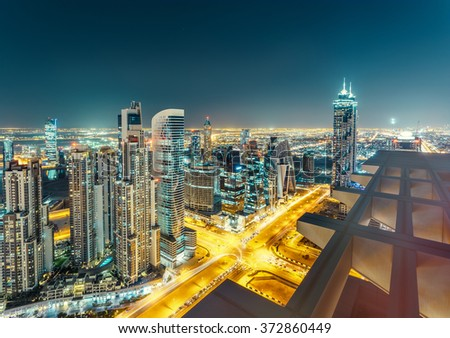 Scenic view from rooftop of Dubai's business bay architecture by night with residential buildings. - stock photo