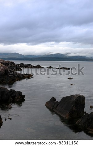 scenic view in kerry ireland of rocks and sea with mountains against a beautiful blue cloudy sky - stock photo